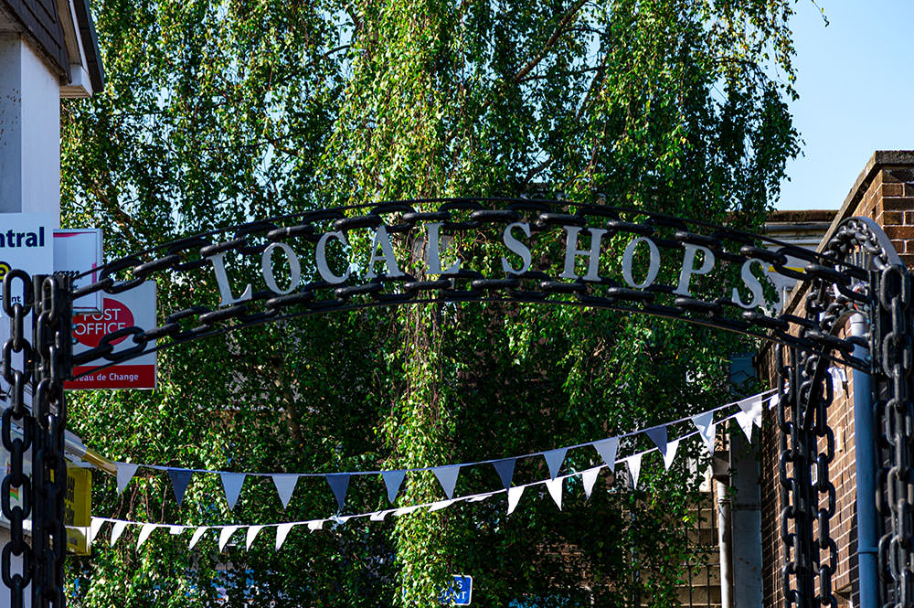 black chain archway with signage saying local shops