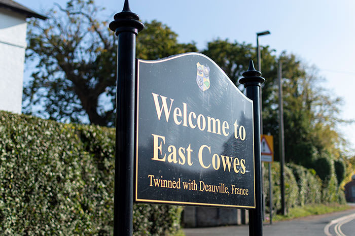 black sign with the words welcome to east cowes